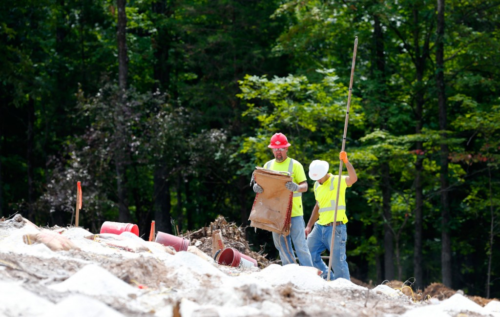 Workers from Austin Powders place charges on the hillside in preparation for blasting (08/23/18)