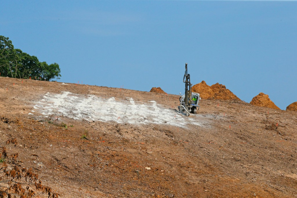 A drilling rig from R&K Excavators prepares holes to accept the explosive charges for blasting to move soil and rock down the hillside. (08/22/18)
